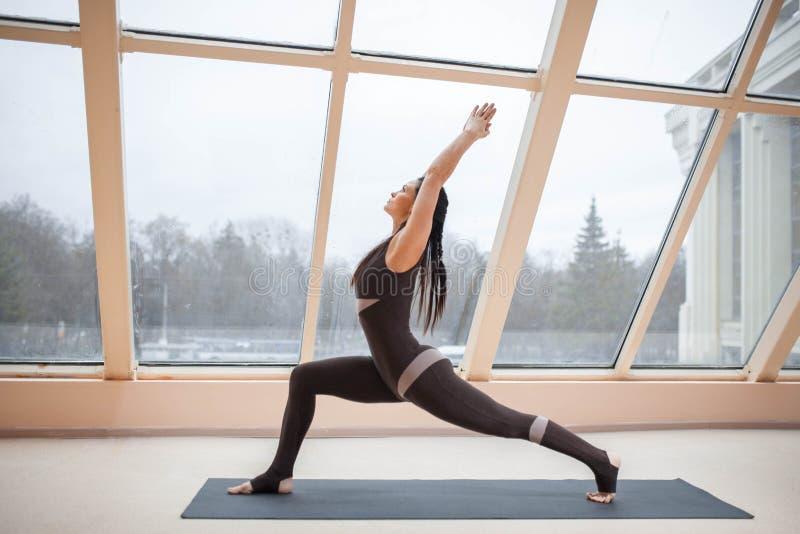 Mulher envelhecida meio que faz a ioga pose na ioga de Virabhadrasana um ou de guerreiro um na esteira na frente das grandes jane fotos de stock