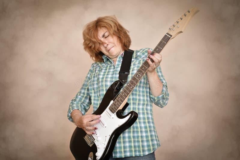 Mulher envelhecida meio que joga a guitarra elétrica imagens de stock royalty free