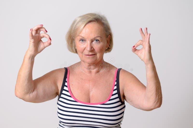 Mulher envelhecida meio que mostra dois sinais aprovados da mão imagem de stock royalty free