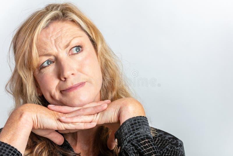 Mulher envelhecida meio que olham inquisidora ou questão foto de stock