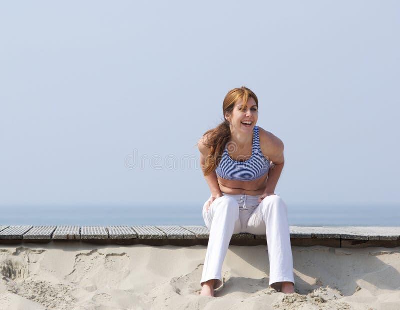 Mulher envelhecida meio que ri da praia fotografia de stock royalty free