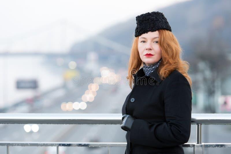 Mulher envelhecida no revestimento preto na barreira da ponte Retrato da mulher urbana O outono gosta de mulheres do vermelho imagens de stock