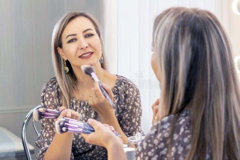 A mulher envelhecida põe sobre sua composição Vista no espelho eu mesmo um maquilhador que aplica o pó na cara com uma grande esc imagem de stock