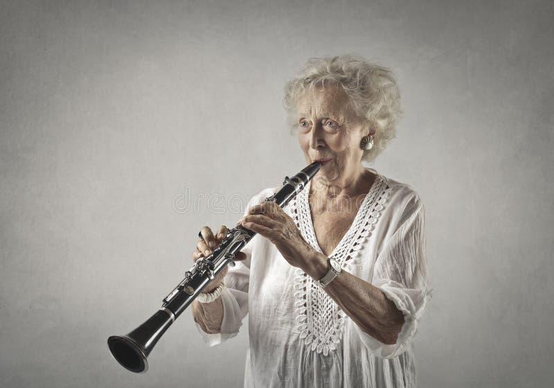 Mulher envelhecida que joga um clarinete fotografia de stock