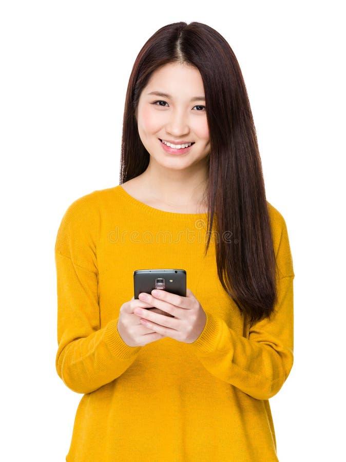 A mulher envia a mensagem através do telefone celular fotos de stock