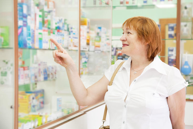 A mulher escolhe drogas na farmácia foto de stock royalty free