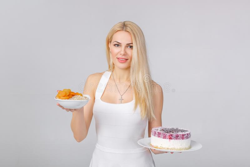 A mulher escolhe entre o bolo e a farinha de aveia fotos de stock royalty free