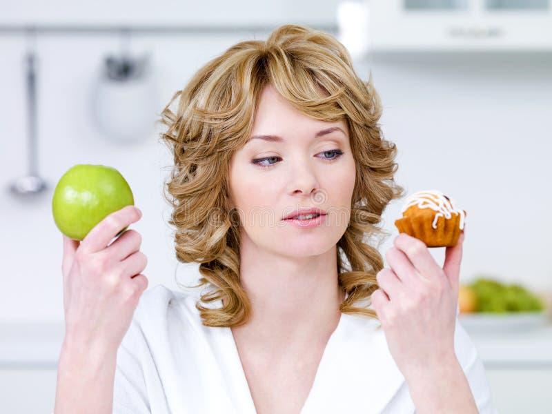 A mulher escolhe entre o bolo e a maçã foto de stock
