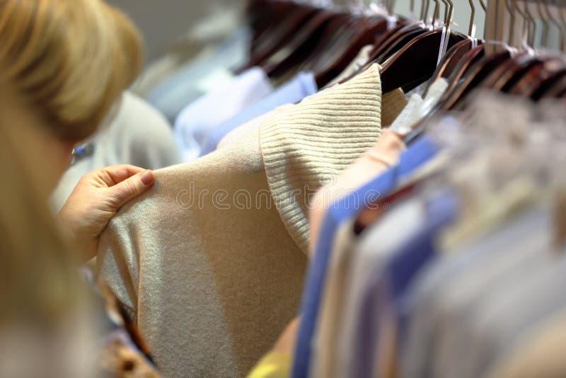 A mulher escolhe a roupa na loja fotografia de stock