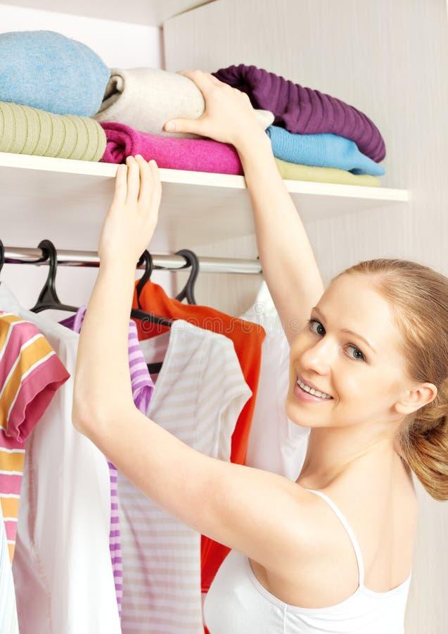 A mulher escolhe a roupa no armário do vestuário em casa fotografia de stock