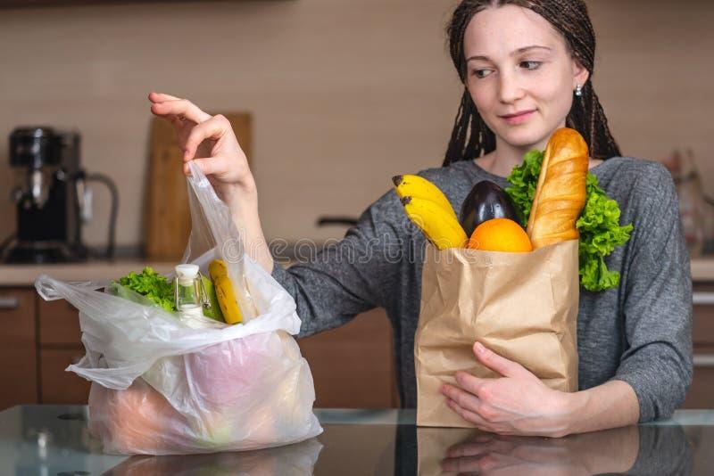 A mulher escolhe um saco de papel com alimento e recusa-o usar o plástico Conceito da prote fotos de stock royalty free
