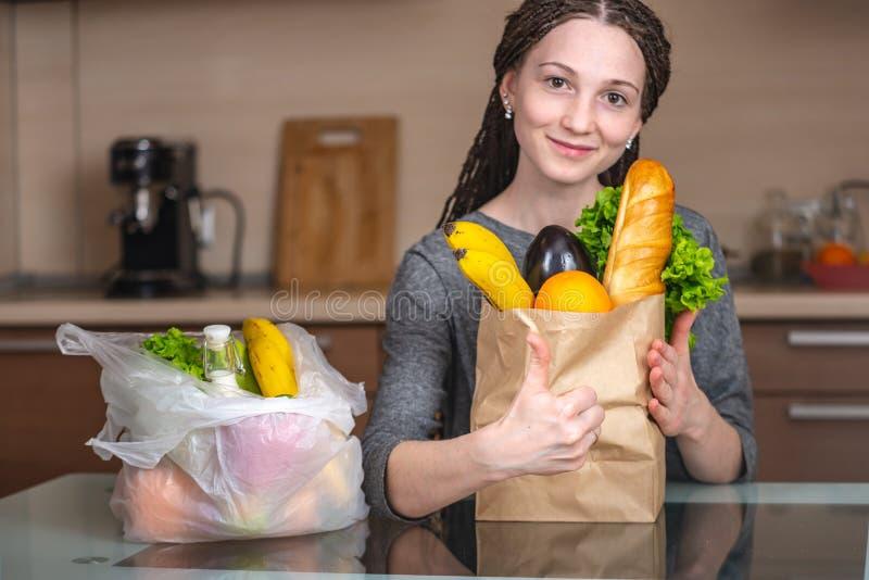 A mulher escolhe um saco de papel com alimento e recusa-o usar o plástico Conceito da prote fotos de stock