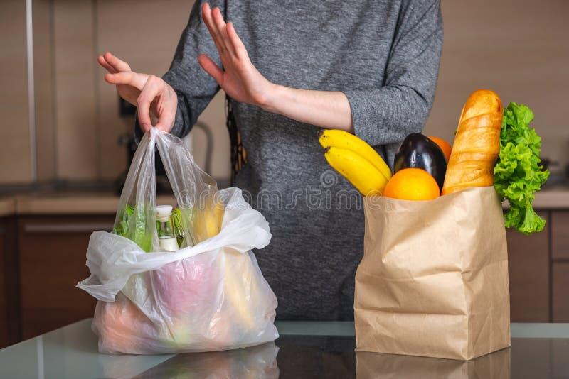 A mulher escolhe um saco de papel com alimento e recusa-o usar o plástico Proteção ambiental e o abandono do plástico fotografia de stock royalty free