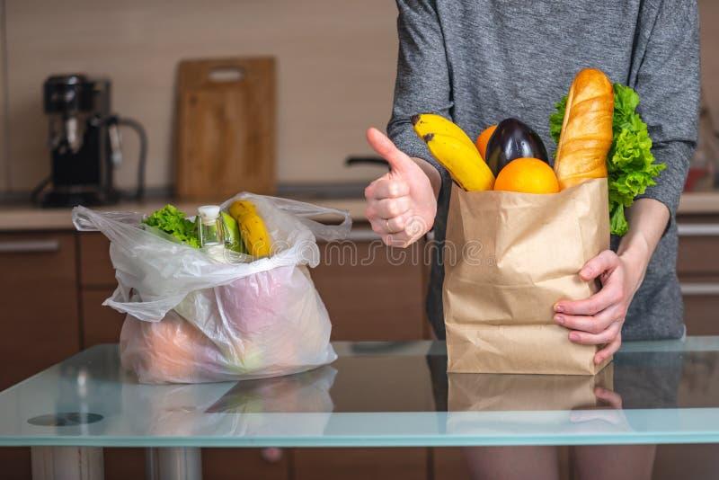 A mulher escolhe um saco de papel com alimento e recusa-o usar o plástico Proteção ambiental e o abandono do plástico fotografia de stock