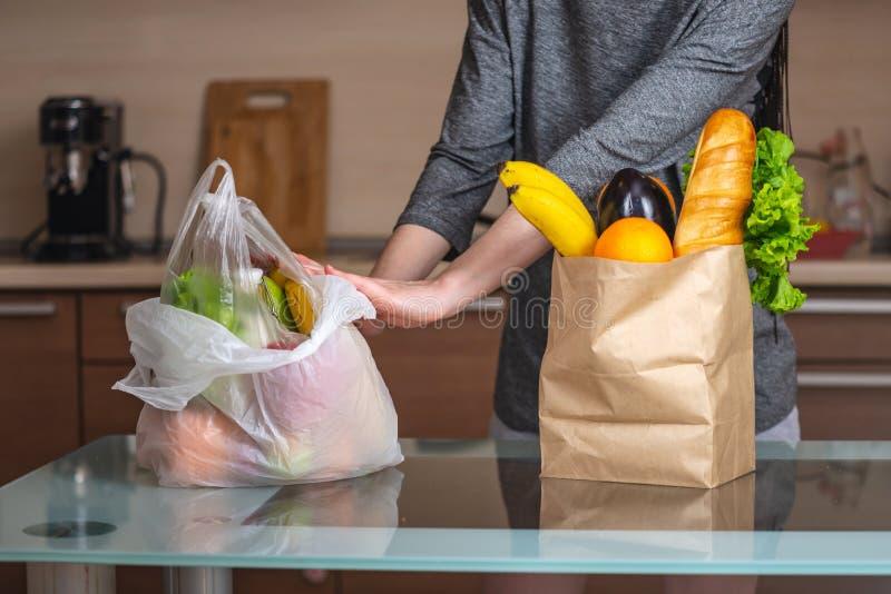 A mulher escolhe um saco de papel com alimento e recusa-o usar o plástico Proteção ambiental e o abandono do plástico imagem de stock