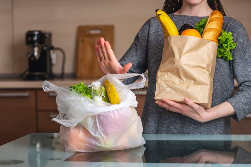 A mulher escolhe um saco de papel com alimento e recusa-o usar o plástico Proteção ambiental e o abandono do plástico imagens de stock royalty free