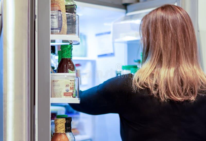 Mulher escolhendo comida do frigorífico aberto fotografia de stock royalty free