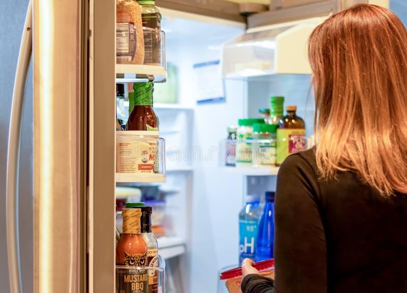 Mulher escolhendo comida do frigorífico aberto imagem de stock royalty free