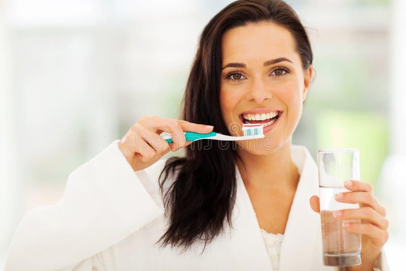 A mulher escova os dentes imagem de stock royalty free