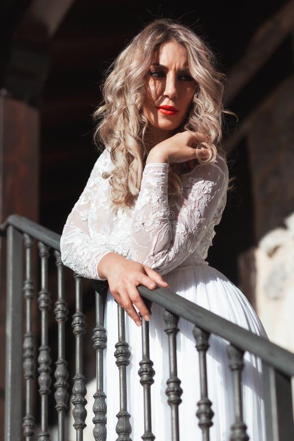 Mulher-escrava em escada Noiva de mulher em vestido branco de noiva Rapariga com olhar de glamour Modelo de moda fotografia de stock
