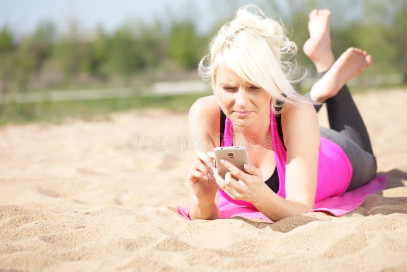 A mulher escreve a mensagem curto na praia fotografia de stock
