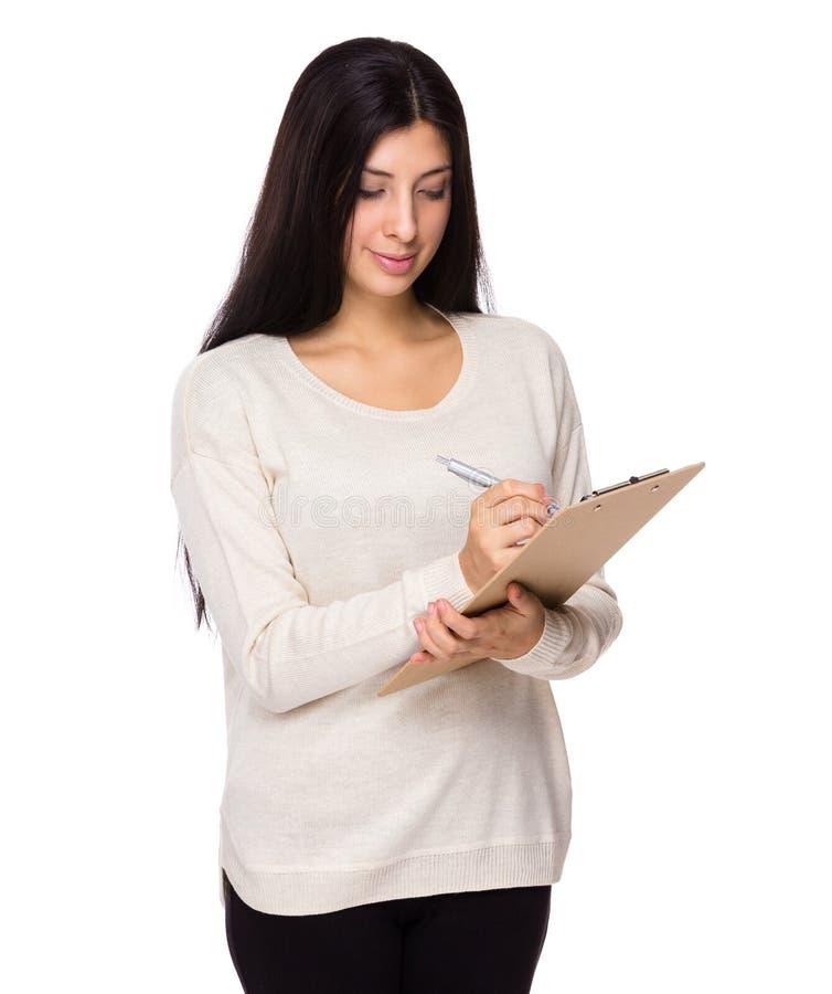 A mulher escreve na prancheta imagem de stock