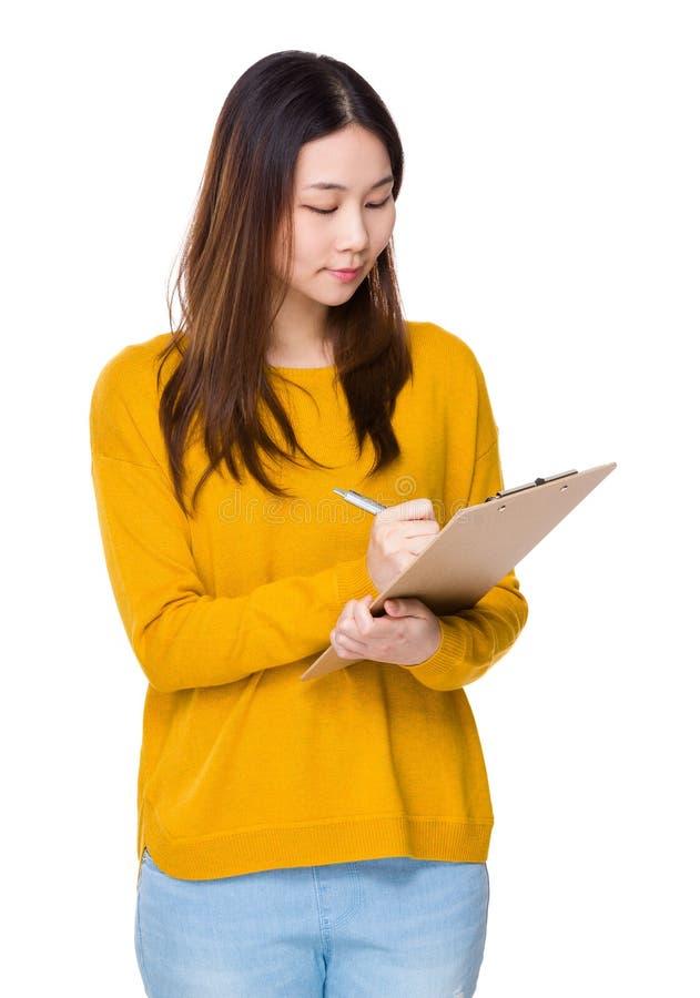 A mulher escreve na prancheta imagens de stock