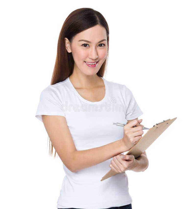 A mulher escreve na prancheta imagens de stock royalty free