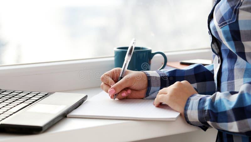 A mulher escreve no caderno imagens de stock royalty free