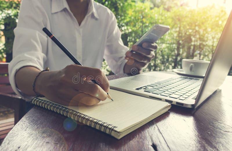 A mulher escreve no caderno e telefone celular guardar com efeito do alargamento da lente do tom do vintage do portátil imagens de stock