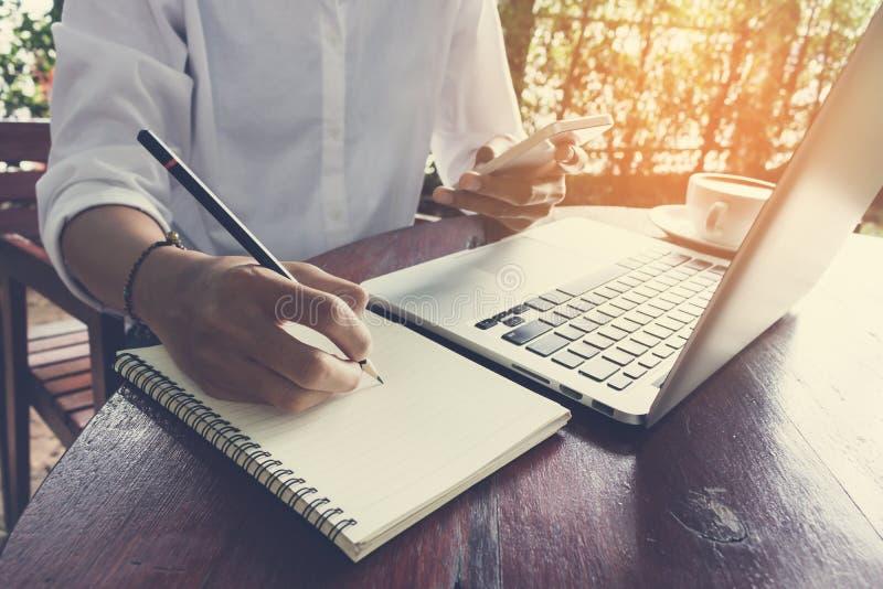 A mulher escreve no caderno e telefone celular guardar com tom do vintage do portátil fotografia de stock royalty free