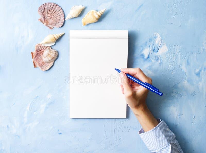 a mulher escreve no caderno na tabela azul de pedra, zombaria acima com quadro da concha do mar, vista superior, planeando o feri fotos de stock royalty free