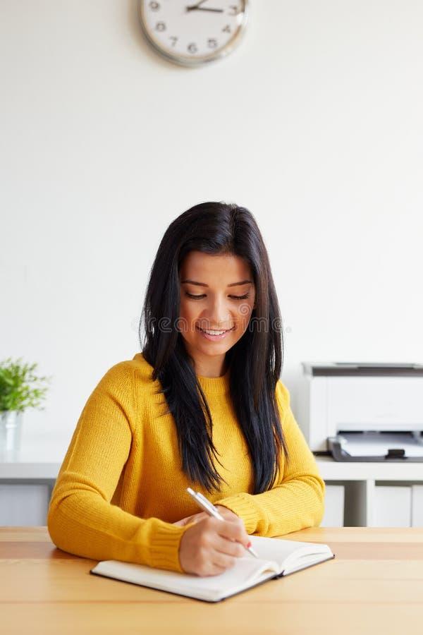 A mulher escreve notas em seu diário imagens de stock