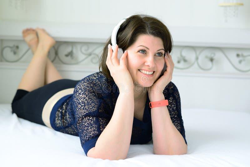 a mulher escuta a música em fones de ouvido e encontra-se na cama fotos de stock royalty free