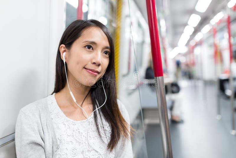 A mulher escuta a música no telefone celular no trem imagens de stock