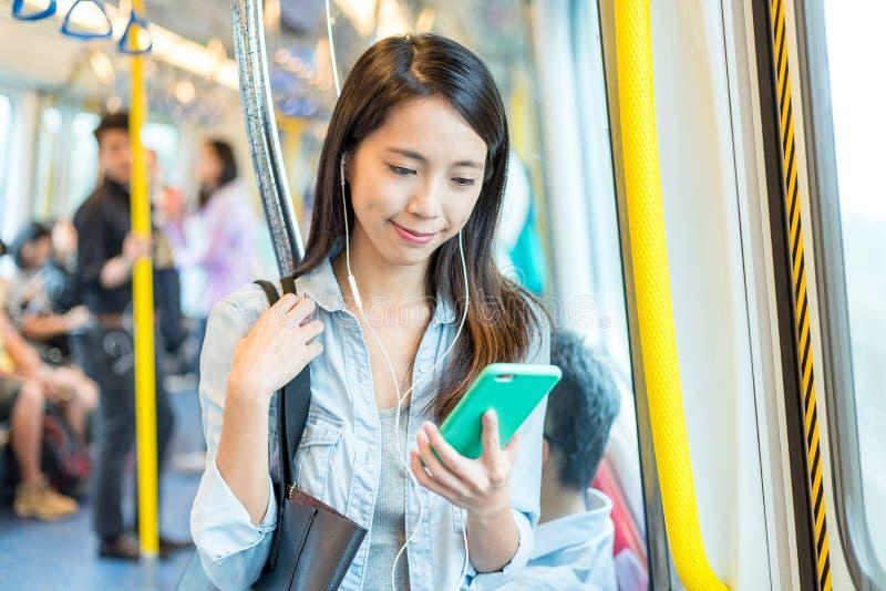 A mulher escuta a música no telefone no trem imagens de stock royalty free