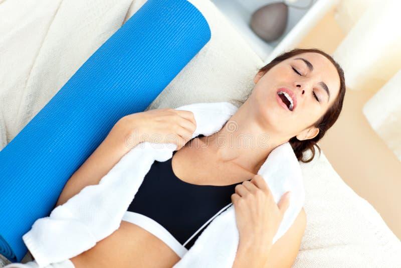 Mulher esgotada que senta-se no sofá após elaborar imagens de stock royalty free