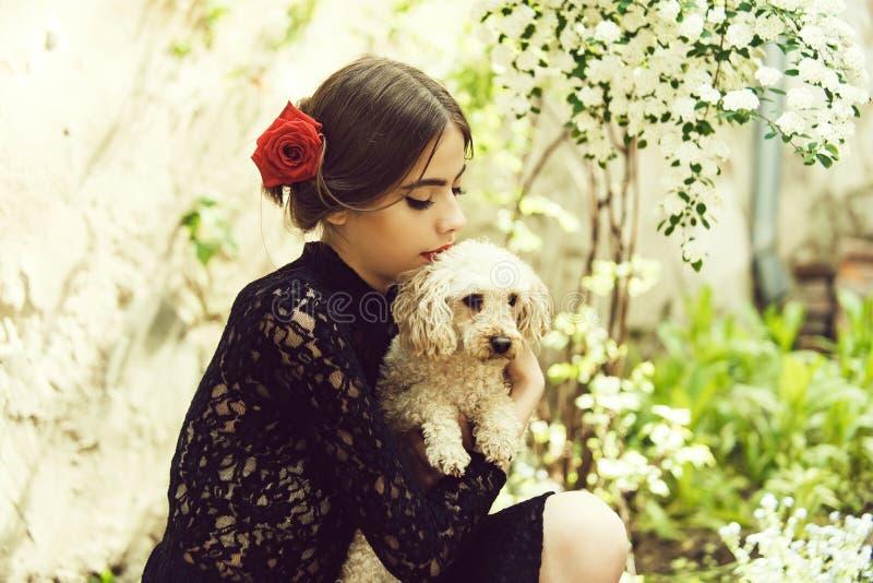 Mulher espanhola ordinária com o animal de estimação do cão de caniche no jardim fotografia de stock