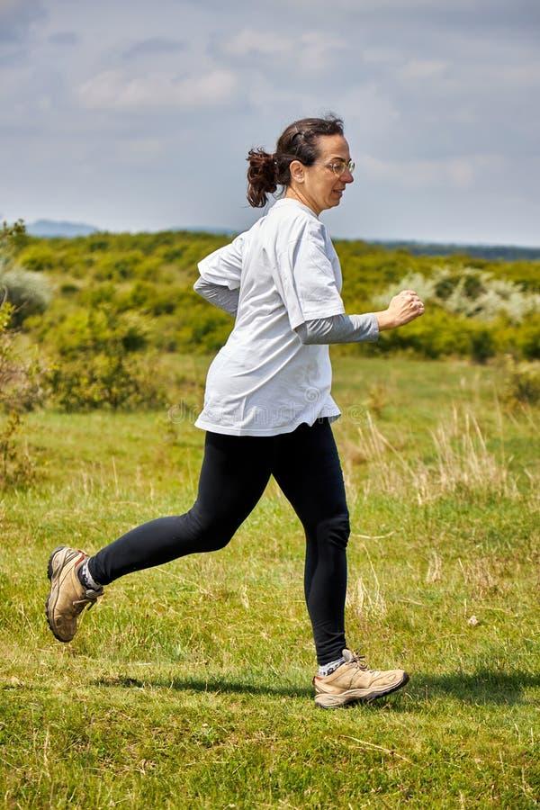 Mulher espanhola que corre no prado imagem de stock royalty free