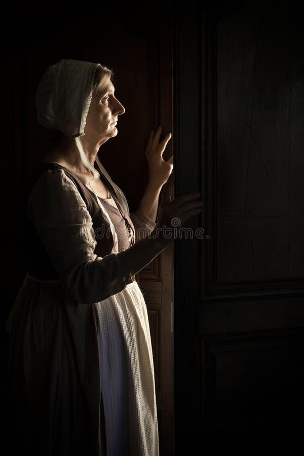 Mulher esperando na porta na escuridão imagens de stock