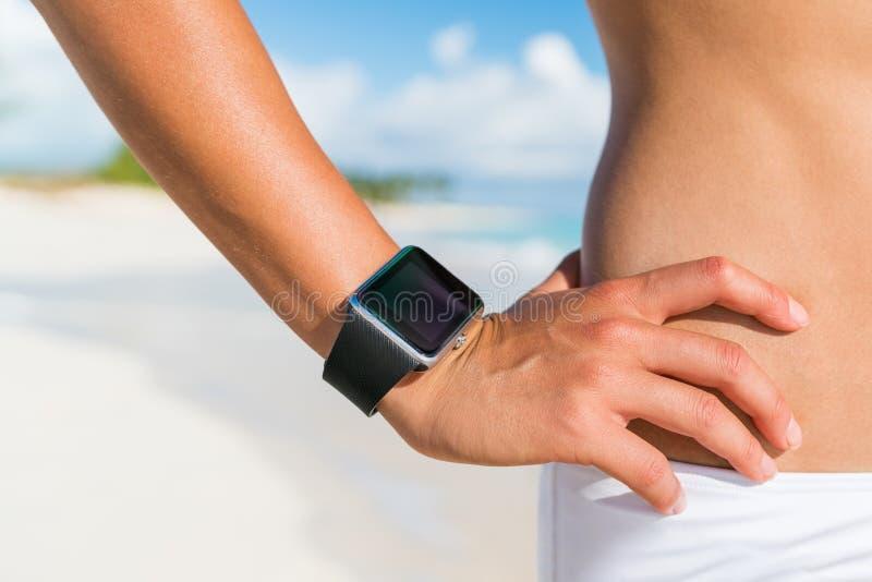 Mulher esperta vestindo relógio inteligente em forma física mostrando tela na praia Pulso e mão em viagem de verão, treinamento d fotografia de stock royalty free