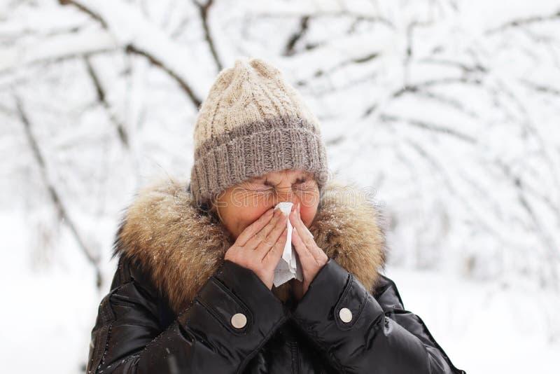 A mulher espirra e funde seu nariz em um lenço fotografia de stock