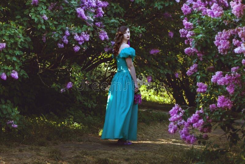 A mulher está andando no jardim do lilás fotos de stock