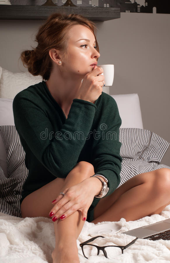 A mulher está bebendo o café em uma cama imagem de stock
