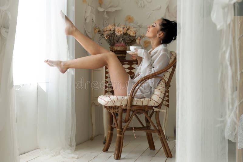 A mulher está bebendo o chá na manhã imagem de stock