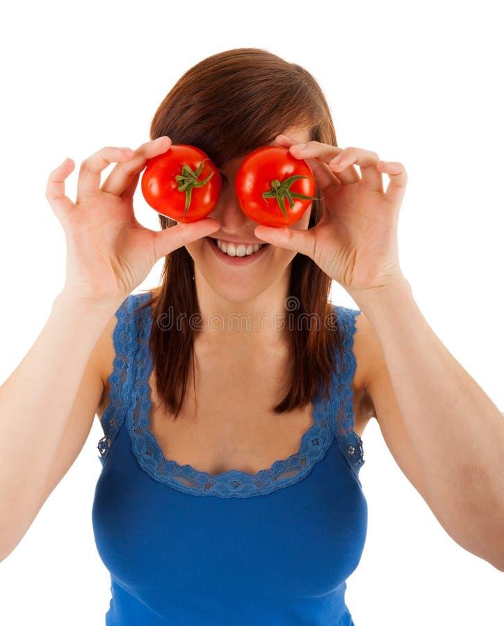 A mulher está cobrindo seus olhos com os tomates fotos de stock royalty free