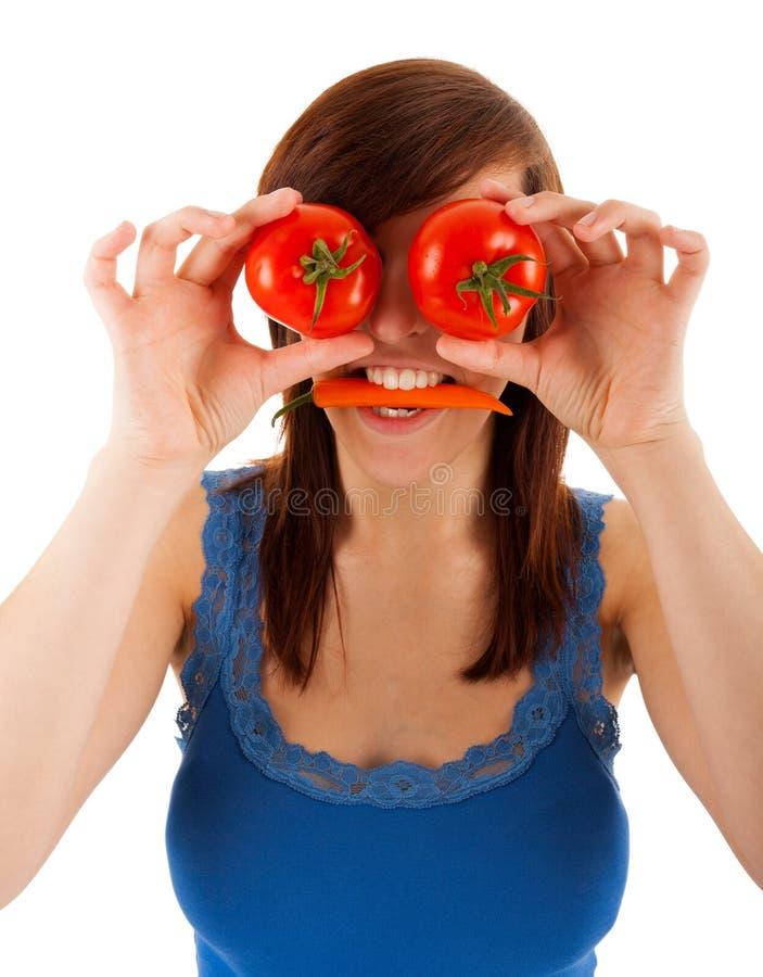 A mulher está cobrindo seus olhos com os tomates fotografia de stock
