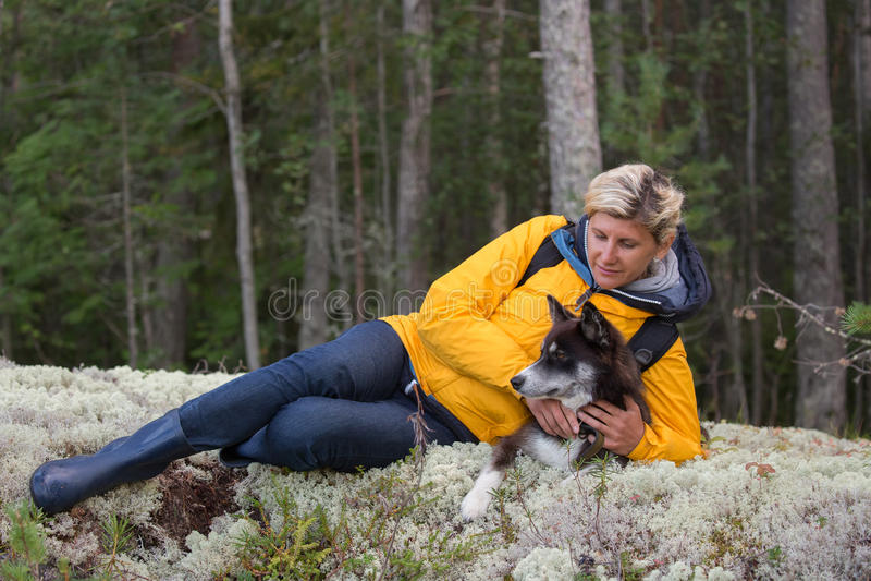 A mulher está colocando no prado da floresta com um cão imagem de stock