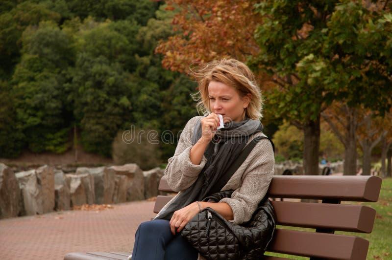 A mulher está com o frio ou a gripe cough fotografia de stock