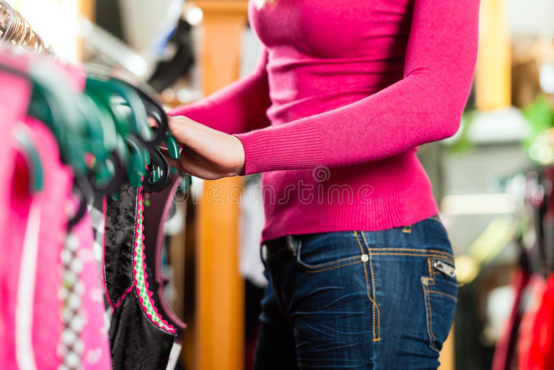 A mulher está comprando Tracht ou dirndl em uma loja fotografia de stock royalty free